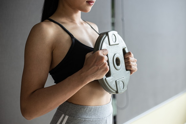 Vrouwen oefenen met haltergewichtplaten in de borst.