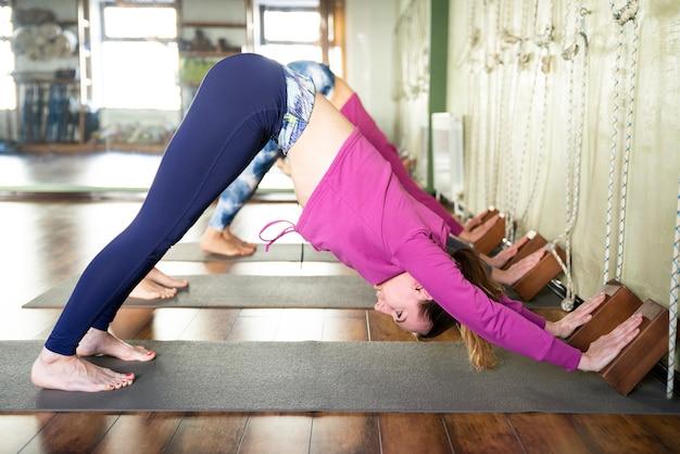 Vrouwen oefenen yoga uitrekken met behulp van houten blokken met handen, oefenen voor wervelkolom en schouders flexibiliteit