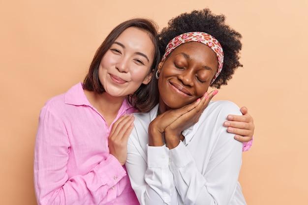 Vrouwen omarmen en kijken voorzichtig naar de camera hebben vriendschappelijke relaties nonchalant gekleed geïsoleerd op bruin
