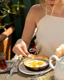 Vrouwen onderdompelend brood in zonnig zij op ei dat in koperpan wordt gekookt