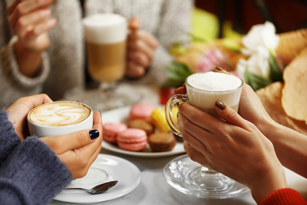 Vrouwen ontmoeten elkaar in café en drinken latte