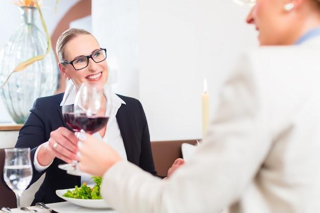 Vrouwen op bedrijfslunch roosteren met wijn