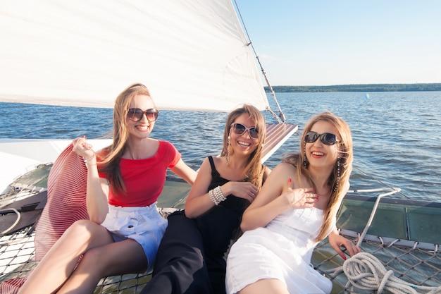 Vrouwen op een jacht met witte zeilen lachen. het concept van zomervakantie op zee en zeilen.