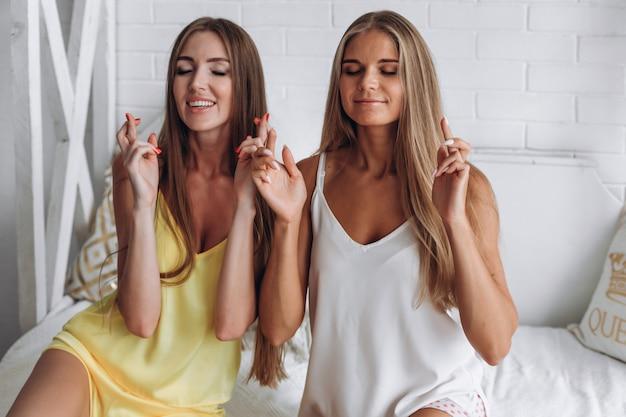 Vrouwen op het bed kruisen vingers