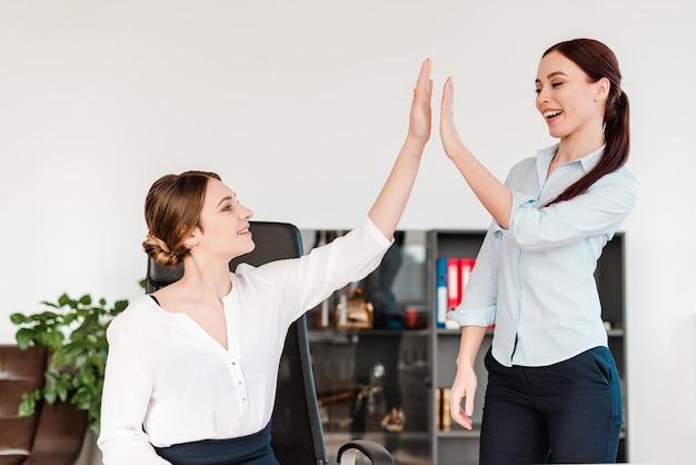 Vrouwen op kantoor geven high five aan elkaar