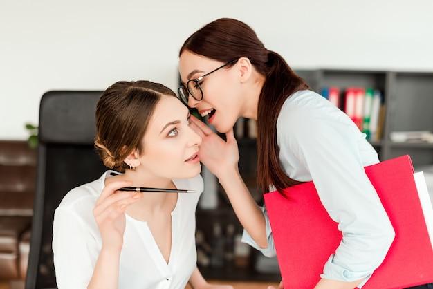Vrouwen op kantoor vertellen elkaar roddels