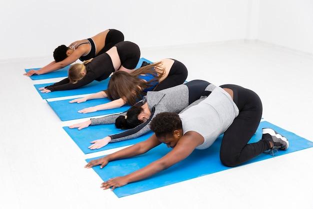 Vrouwen op mat die uitrekkende oefening doen