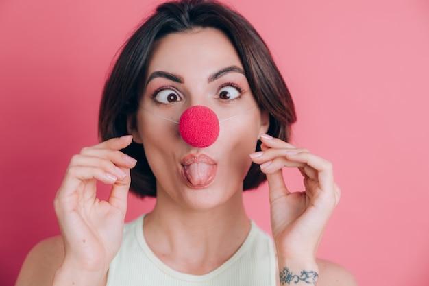 Vrouwen op roze achtergrond vrij grappige en glimlachende jonge vrouw die clownneus, partijstemming dragen