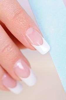 Vrouwen oppoetsende spijker op wijsvinger met nailfile - macro