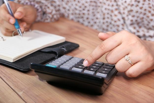 Vrouwen overhandigen met behulp van calculator op bureau.