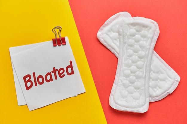 Vrouwen pads op rood met een sticker en het opschrift opgeblazen op geel