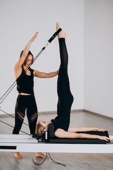Vrouwen pilates doen op een hervormer