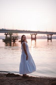 Vrouwen poseren bij zonsondergang fulllength portret van een mooie jonge vrouw poseren bij zonsondergang op het strand ...