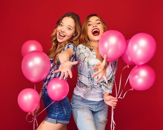Vrouwen poseren met grote geschenkdoos en roze ballonnen