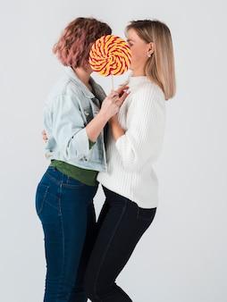 Vrouwen poseren met lolly voor valentijnskaarten