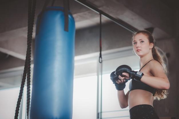 Vrouwen poseren voor bokstraining in de fitnessruimte