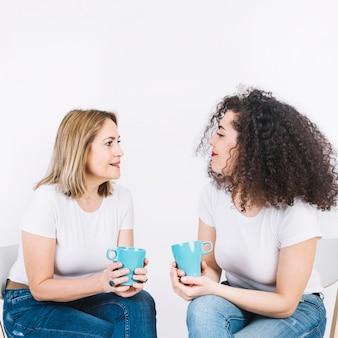 Vrouwen praten met mokken