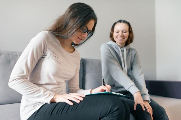 Vrouwen professionele psycholoog die met tienermeisje spreekt