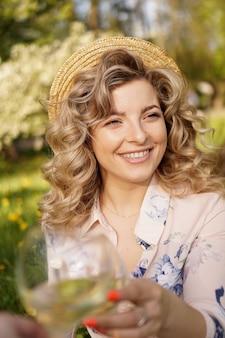 Vrouwen rammelende bril met lekkere wijn op lichte achtergrond op zomerdag. gelukkig blonde met krullend haar in een strooien hoed