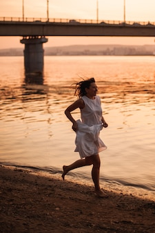 Vrouwen rennen bij zonsondergang een charmante jonge vrouw in een witte zomerjurk die blootsvoets op de sa...