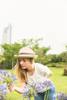 Vrouwen ruikende bloemen in tuin