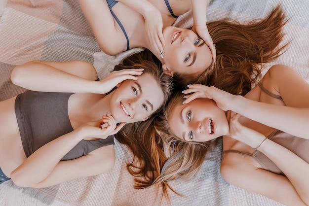Vrouwen rusten en hebben plezier. vriendinnen lachen thuis liggend op de vloer op kussens. boommeisjes maken zelfgemaakte gezichts- en haarschoonheidsmaskers. vrouwen zorgen voor een jeugdige huid.