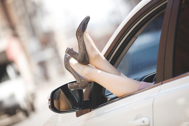 Vrouwen` s voeten in de auto. onherkenbare vrouw in de auto. dame` s schoenen uit het auto` s venster. vrouwelijke benen.