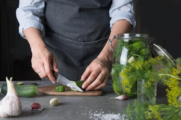 Vrouwen scherpe komkommers voor groenten in het zuur met knoflook en dille. detailopname. detailopname.