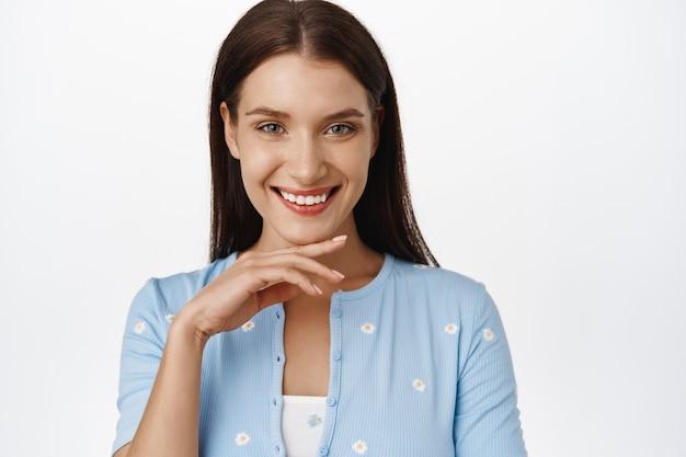 Vrouwen schoonheid. close-up portret van aantrekkelijke volwassen 30s vrouw, schone, gloeiende huid aan te raken zonder rimpels en lachende witte perfecte tanden, stanidng op wit