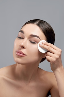 Vrouwen schoonmakend gezicht met stootkussen