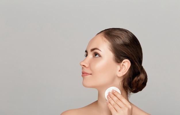 Vrouwen schoonmakend gezicht met wit stootkussen. mooi meisje make-up verwijderen witte cosmetische wattenschijfje. gelukkig lachend vrouw make-up van de gezichtshuid met cosmetische pad opstijgen. gezichtsverzorging.