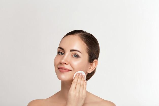Vrouwen schoonmakend gezicht met wit stootkussen. mooi meisje make-up verwijderen witte cosmetische wattenschijfje
