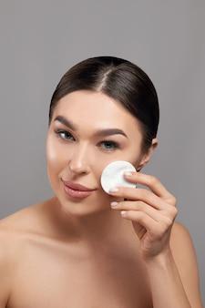 Vrouwen schoonmakend gezicht met wit stootkussen