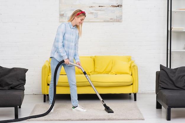 Vrouwen schoonmakend tapijt met vacuüm