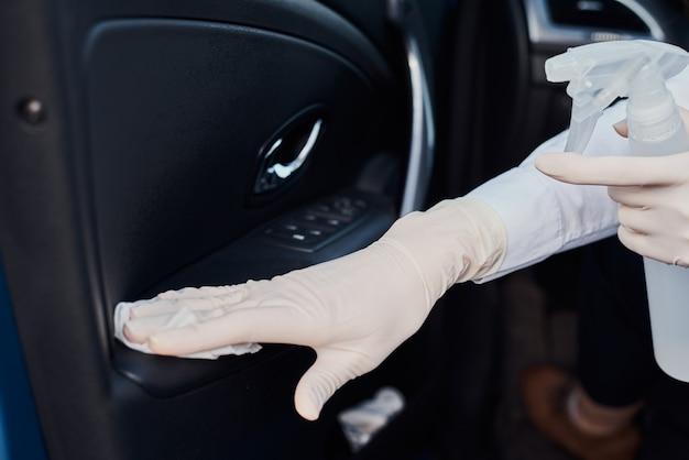 Vrouwen schoonmakende auto met desinfectiespray om tegen coronavirus te beschermen