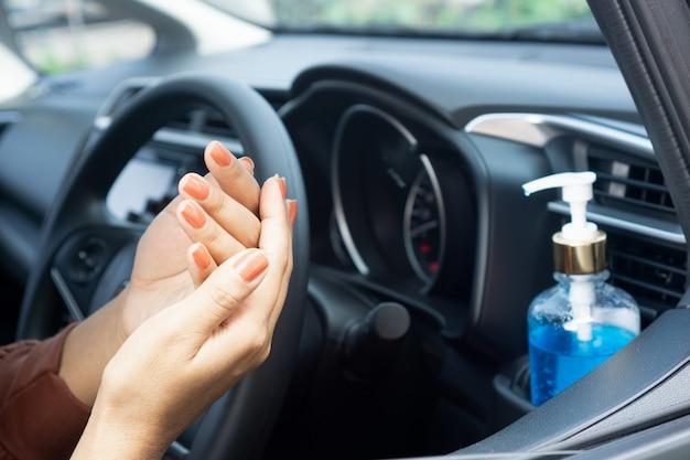 Vrouwen schoonmakende hand met alcoholgel alvorens auto te drijven
