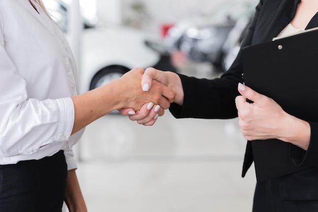 Vrouwen schudden handen in auto showroom