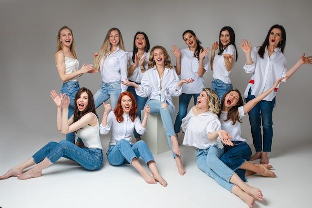 Vrouwen solidariteit concept. gelukkig jong vrouwelijk team stijlvol personeel poseren het dragen van spijkerbroek