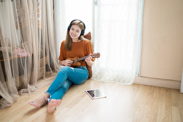 Vrouwen spelen gitaar in de woonkamer thuis