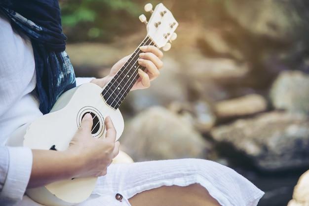 Vrouwen spelen ukulele die nieuw is voor de waterval