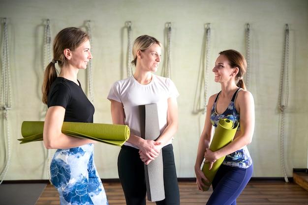 Vrouwen staan bij een muur met oefenmatten