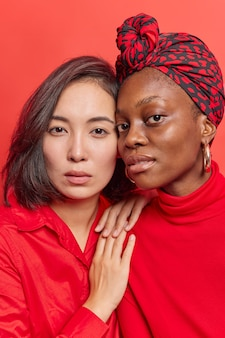 Vrouwen staan dicht bij elkaar kijken met zelfverzekerde uitdrukkingen op camera dragen rode kleren hebben een goede relatie. vrouwelijke modellen van gemengd ras poseren binnen. diversiteitsconcept