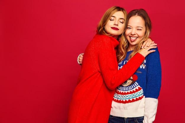 Vrouwen staan in stijlvolle winter warme truien op rode muur