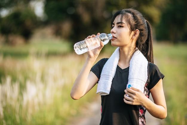 Vrouwen staan na het sporten water te drinken