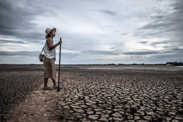 Vrouwen staan op droge grond en vistuig, opwarming van de aarde en watercrisis