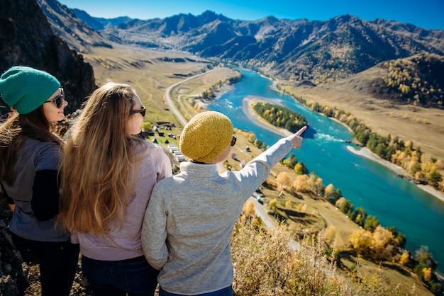 Vrouwen staan op een heuvel en kijken naar een bergrivier