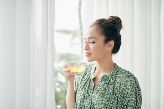 Vrouwen staan voor ramen en houden 's ochtends een kopje thee vast