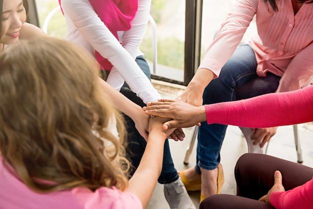 Vrouwen steken hun handen in de vergadering van borstkankerbewustmakingscampagnes