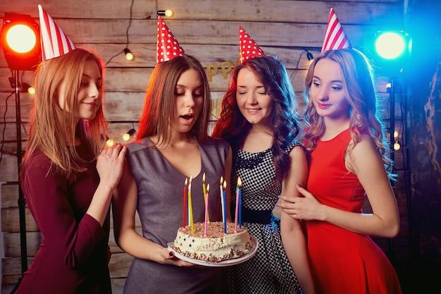 Vrouwen steken kaarsen aan op de taart met champagne in de hand