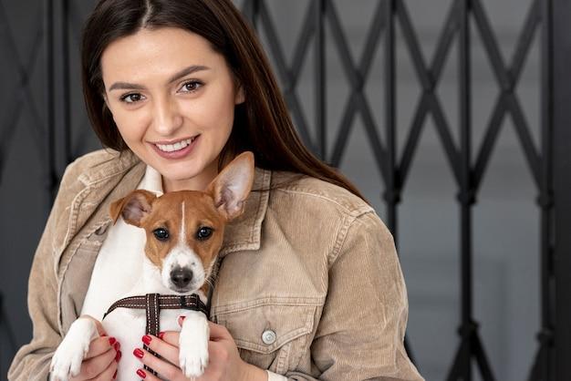 Vrouwen stellende buitenkant met haar hond